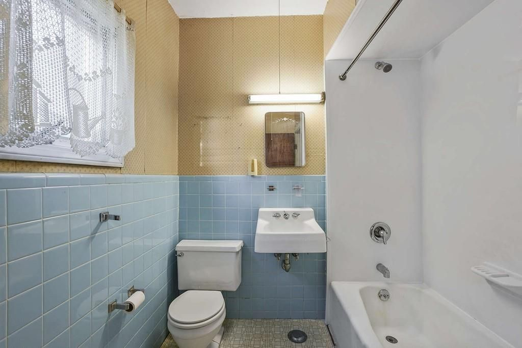 A small bathroom with no curtain on the shower.