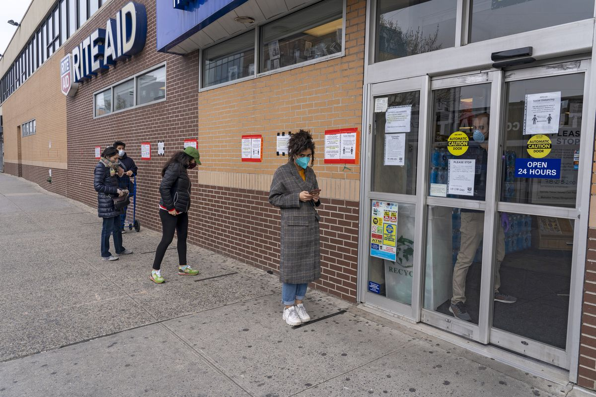 People in a socially distanced line stand outside a pharmacy.