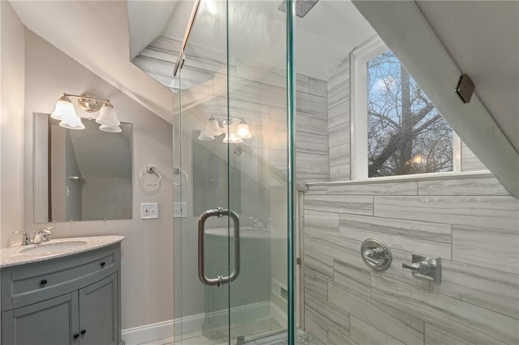 A tiled bathroom with grey and glass and a large window.