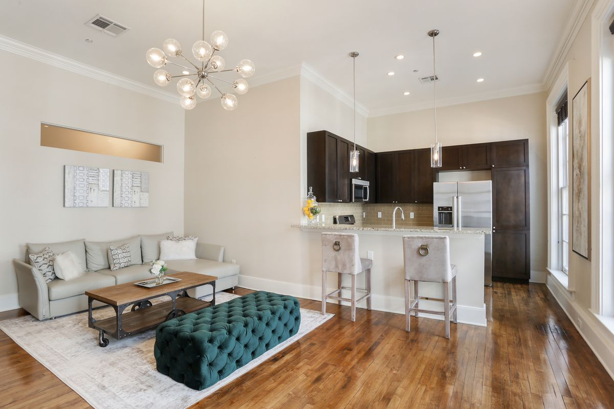 An open living area and kitchen with wood floors and modern light fixtures