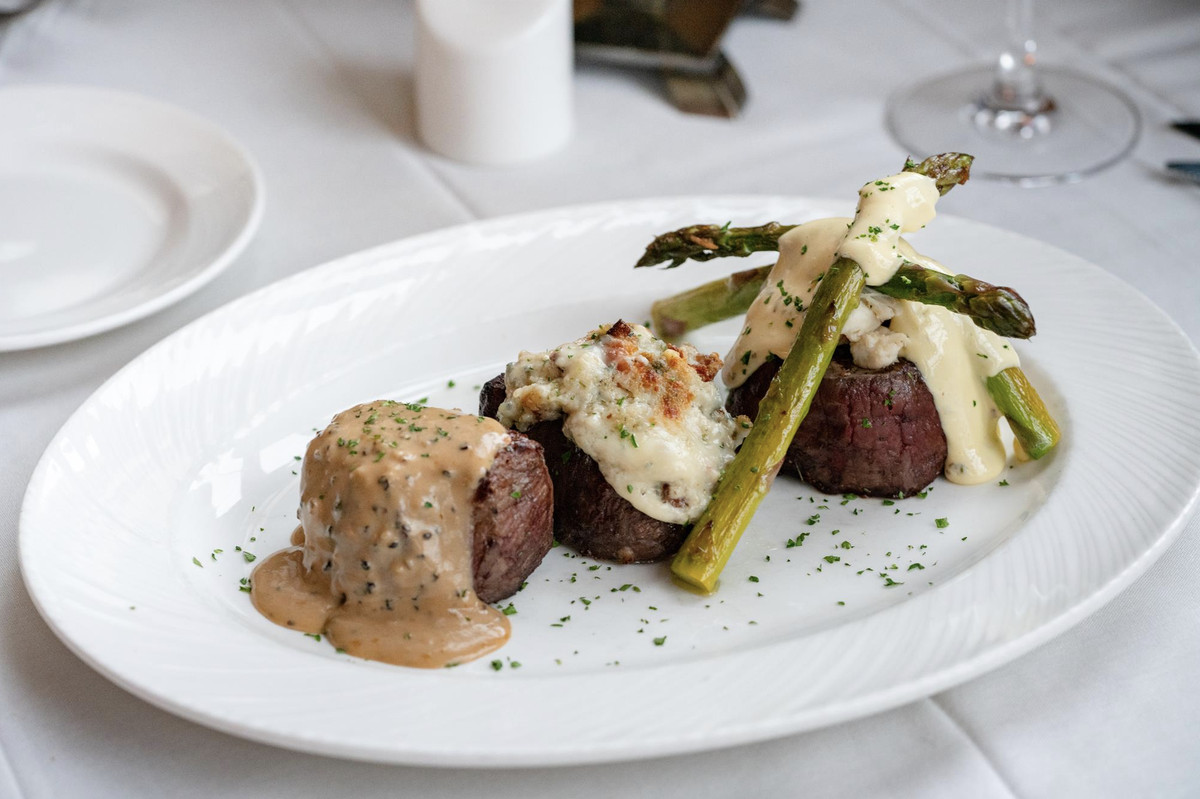 Three cubes of steak sit on a plate, dressed with some sort of white goop, and adorned with asparagus spears