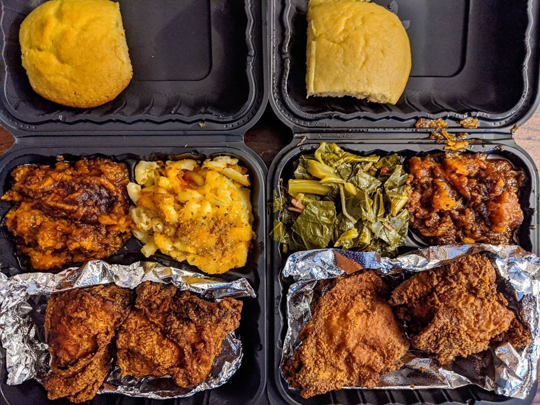 Overhead view of two black takeout containers of fried chicken with sides (mac and cheese and candied yams in one container, candied yams and collard greens in the other)