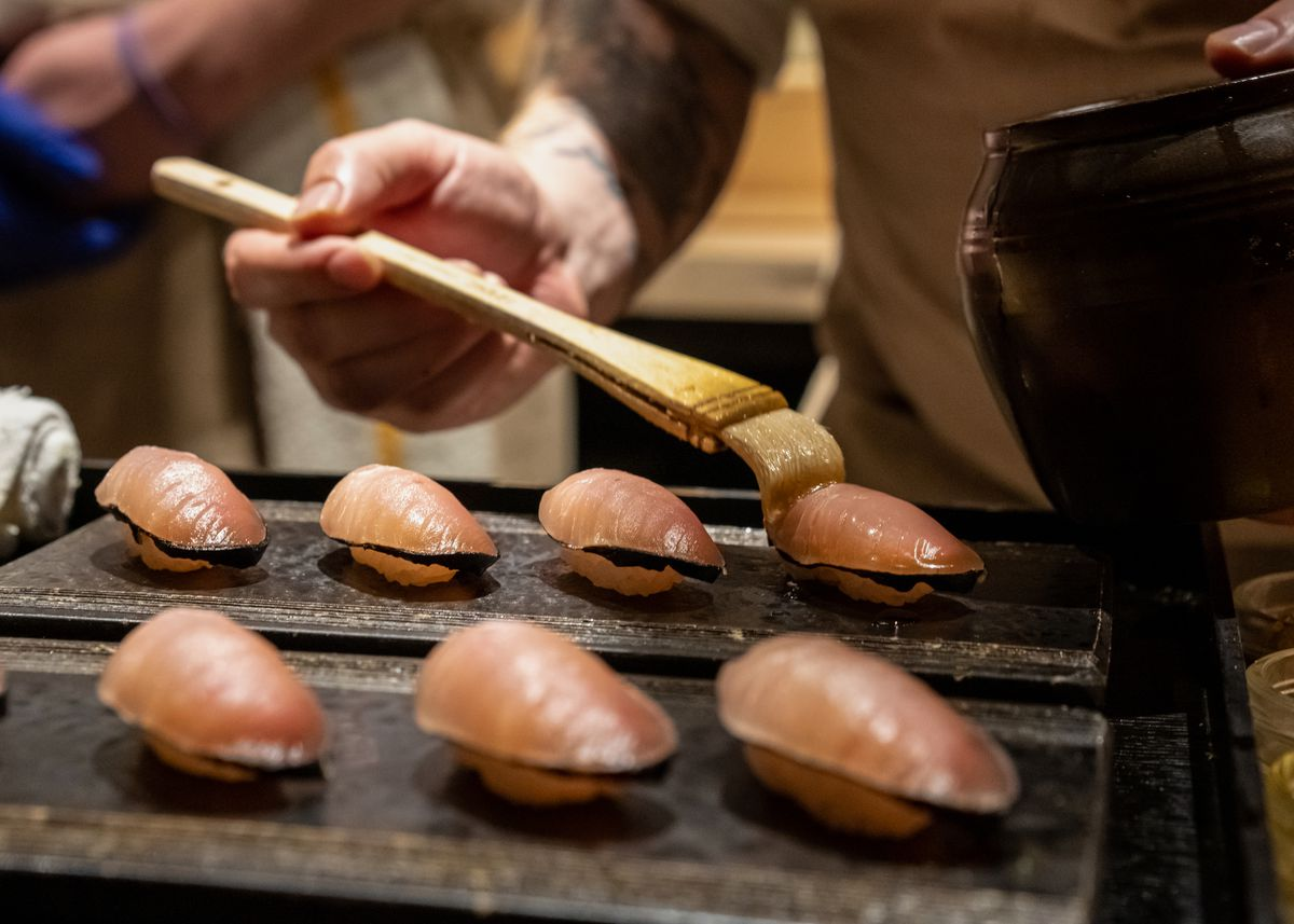 Seven pieces of a pink fish sushi and a person is brushing an oil onto one of the pieces