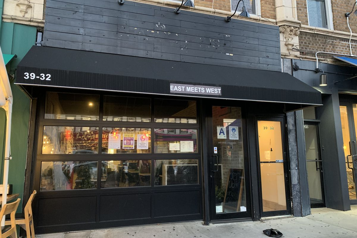 """The front of a restaurant, whose black awning reads """"East Meets West."""" Off-screen to the left, chairs and part of an outdoor seating area are visible."""