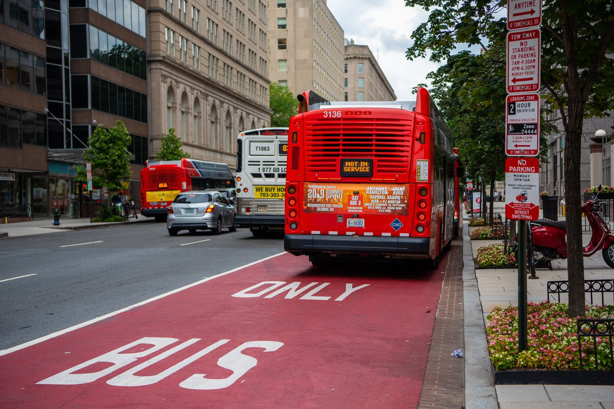 """A bus seen from behind in a """"bus only"""" lane painted red in the midst of a city."""