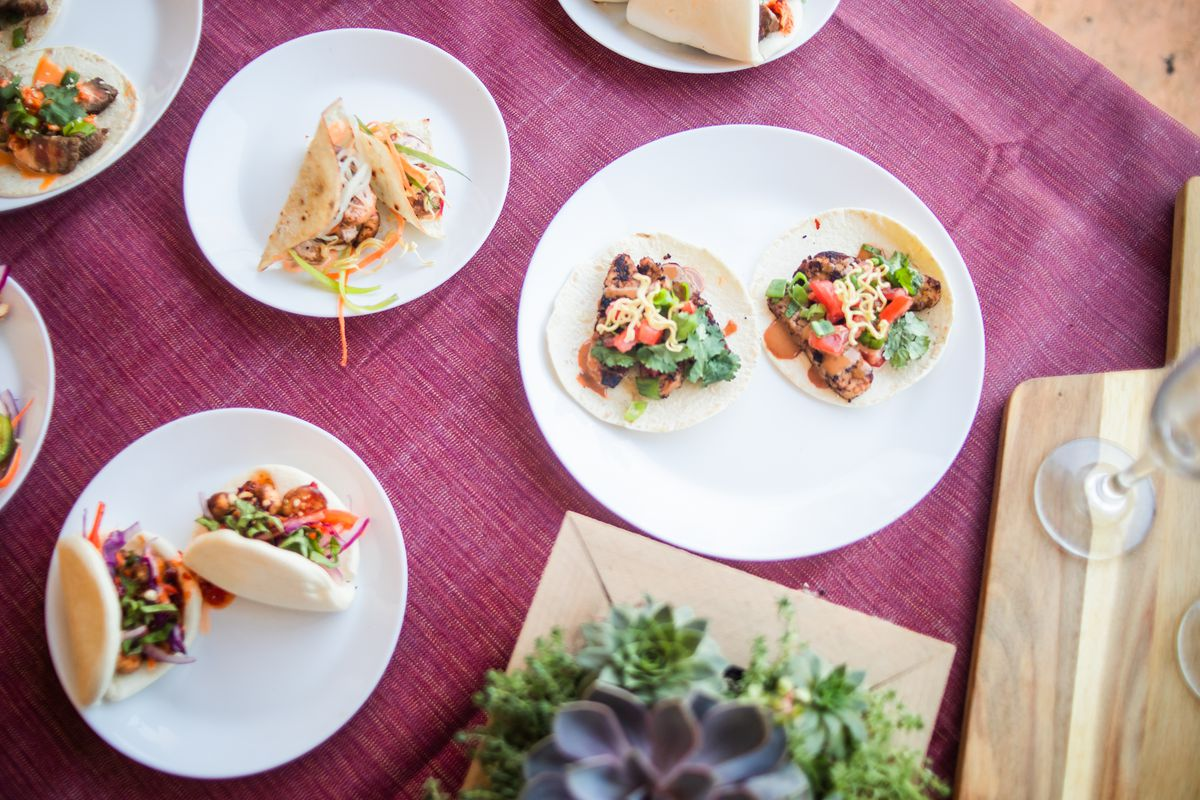 Plates of tacos and bao sit on a table, which is covered with a purple cloth.