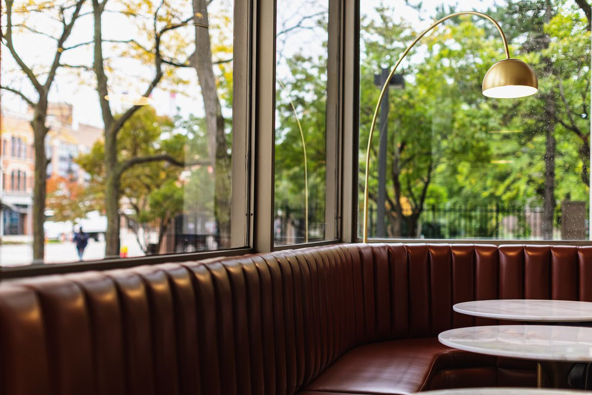 Brown upholstered booths line the corner along the large windows at Hammer & Nail. Brass light fixtures curve over the top of the booths.