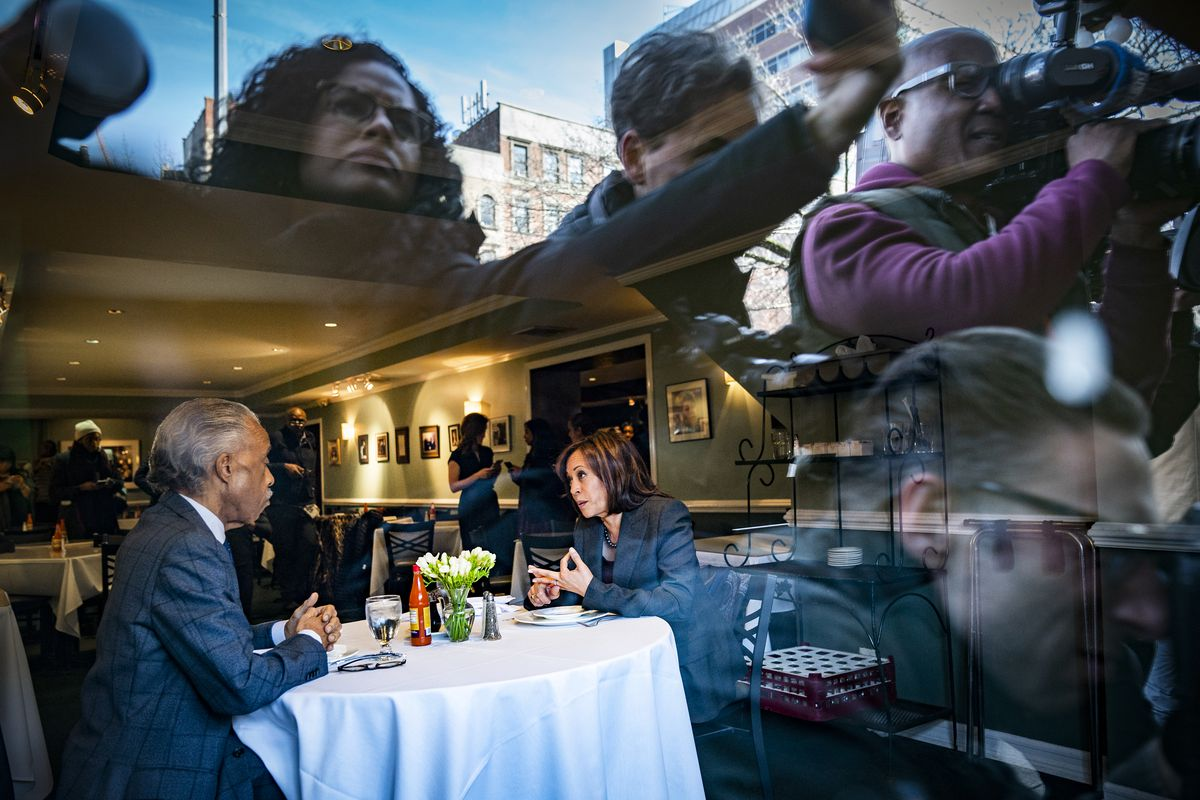 Reporters are reflected in a window as Rev. Al Sharpton and 2020 Democratic presidential candidate Sen. Kamala Harris (D-CA) talk while having lunch at Sylvia's Restaurant in Harlem, New York City, on February 21, 2019.