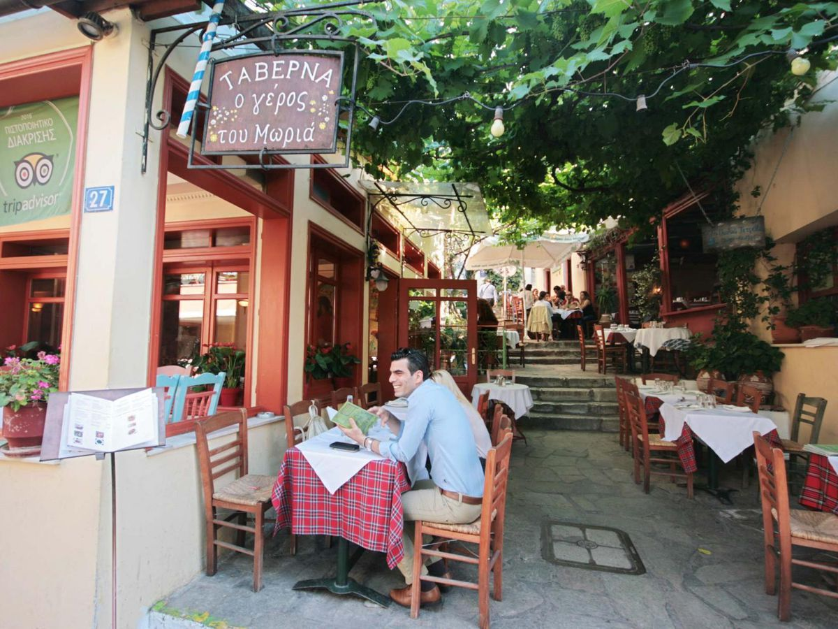 A restaurant exterior, with people seated at outdoor tables down a winding corridor in the sun