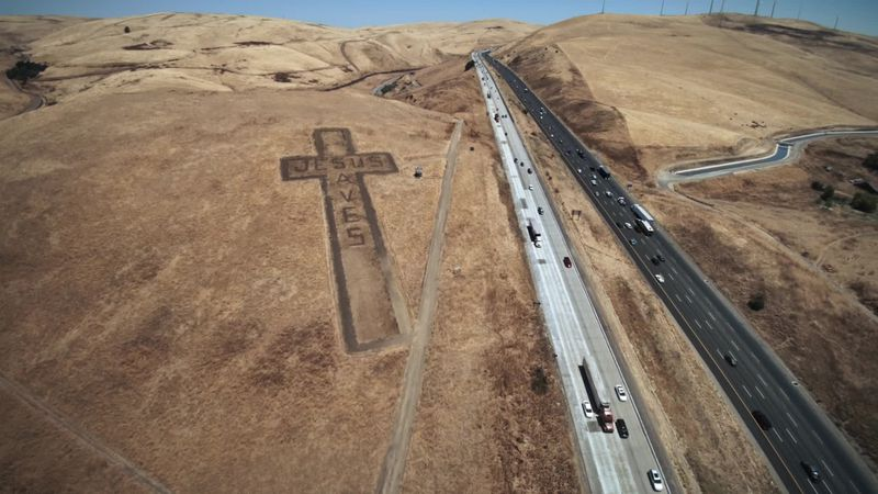 An aerial view of a highway with a giant cross by the side of the road from Strange Negotiations.