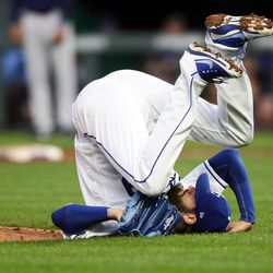 Jason Hammel rolls over after being hit by a ball off the bat of Lorenzo Cain.