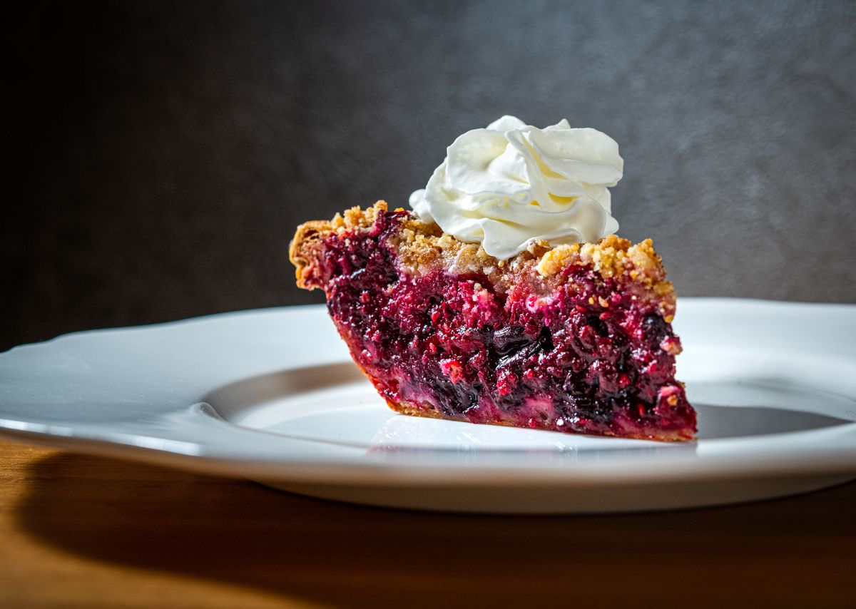 A gorgeous mixed berry pie with a dollop of whipped cream