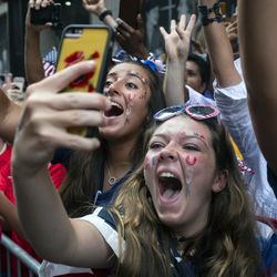 Fans celebrate as members of the the U.S. women's soccer team pass by during a ticker tape parade in New York City.
