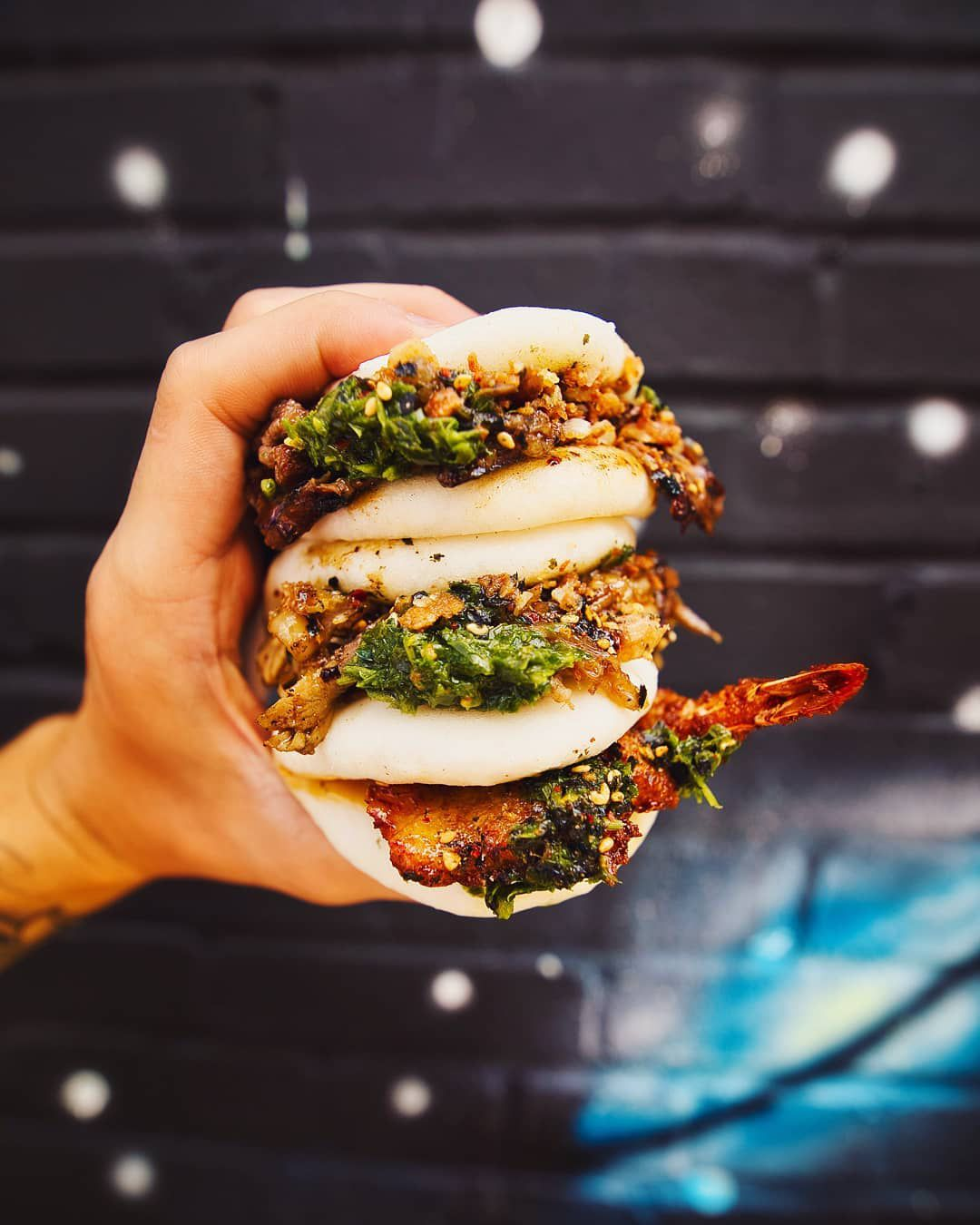 A hand firmly holding three baos comprising Korean beef bulgogi, coconut shrimp, and duck confit, a red shrimp tail juts out from the bottom boa