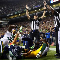 Officials signal after Seattle Seahawks wide receiver Golden Tate pulled in a last-second pass for a touchdown from quarterback Russell Wilson to defeat the Green Bay Packers 14-12 in an NFL football game, Monday, Sept. 24, 2012, in Seattle. The touchdown call stood after review.