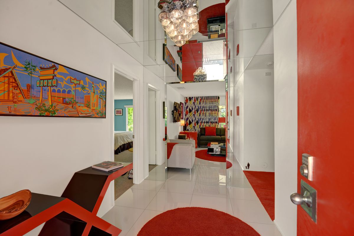 A foyer with white floors, lots of red pops of color, and mirrored ceilings.