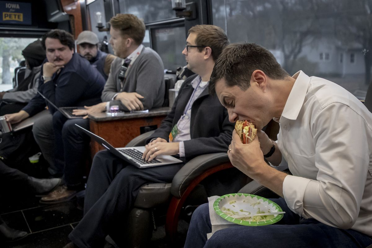 Buttigieg eating an Italian sub on the bus.