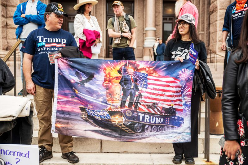 Protesters wearing Trump t-shirts hold a flag bearing an image of President Donald Trump on a tank in front of an American flag. They're standing on the steps of the Texas State Capitol building on April 18, 2020 in Austin, Texas, where protesters have gathered to call for the country to be opened up despite the risk of COVID-19.