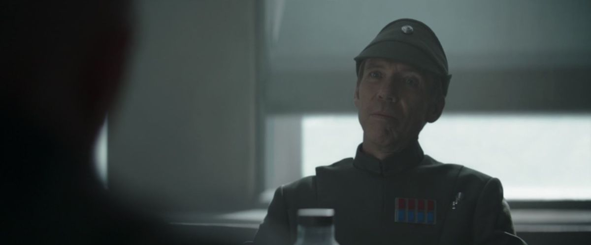 An Imperial officer glares at Mig Mayfeld over a table in a mess hall on some godsforsaken planet.
