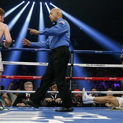 Referee Joe Cortez directs Canelo Alvarez, of Mexico, to a corner after he knocked down Josesito Lopez during the second round of a super welterweight championship boxing match on Saturday, Sept. 15, 2012, in Las Vegas. Alvarez won the match.