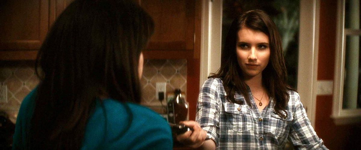 jill (emma roberts) holds a knife to her friends chest as she casts a sinister look in the kitchen