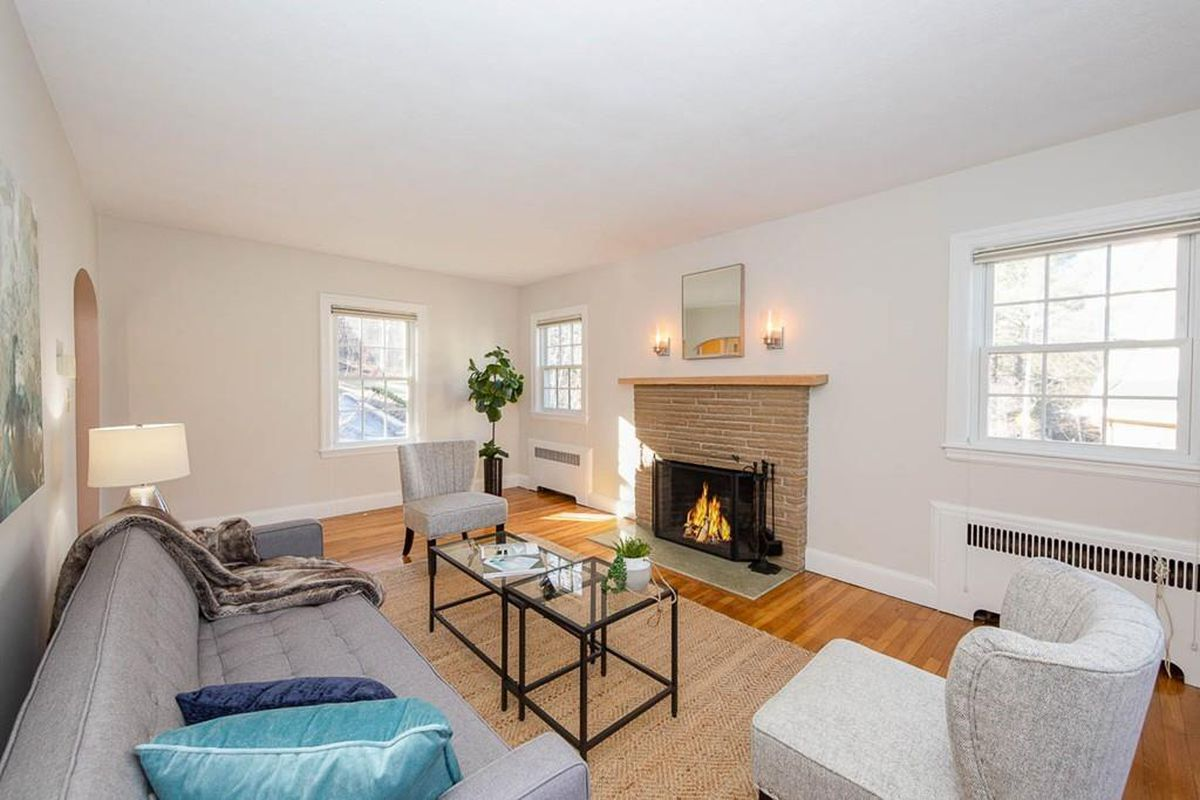 A sizable living room with a couch and a chair arranged facing a fireplace.