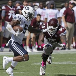 Brigham Young defensive back Dayan Ghanwoloku (5) runs back an intercepted pass past Mississippi State offensive lineman Greg Eiland (58) during the second half of an NCAA college football game in Starkville, Miss., Saturday, Oct. 14, 2017. Mississippi State won 35-10. (AP Photo/Jim Lytle)