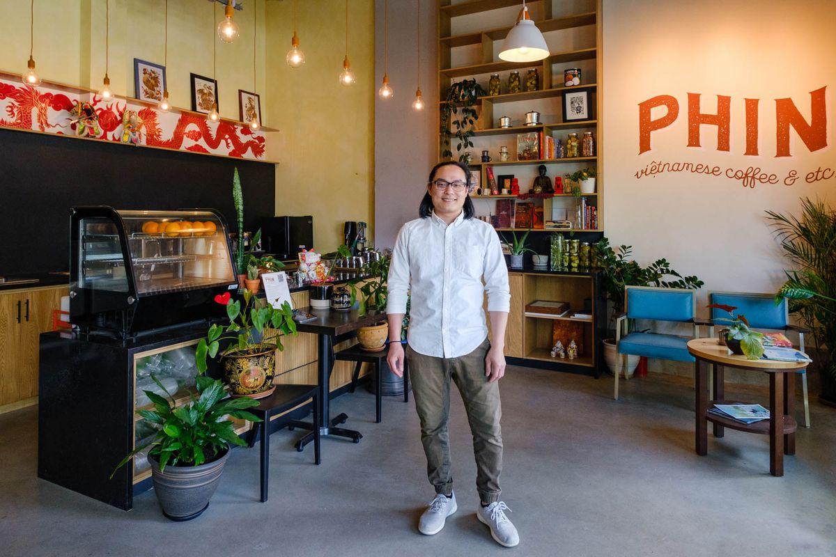 阮宝(音译)站在咖啡馆的中央,Phin,穿着灰色裤子和一件卷起的衬衫