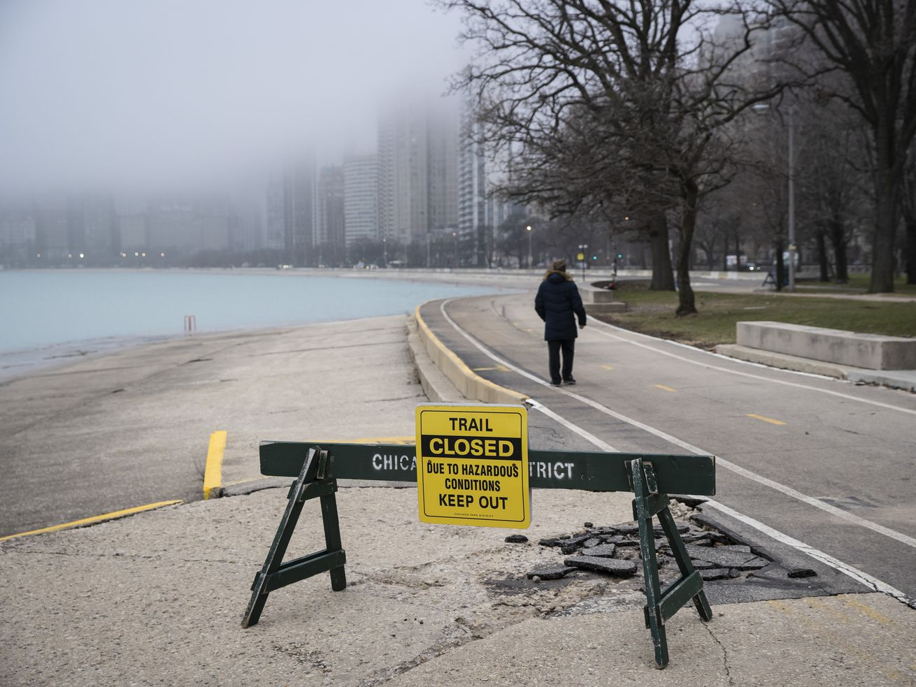 "A man ignores a ""trail closed"" sign on the Lakefront Trail near Oak Street Beach as the city closes the area to pedestrians amid fears of the coronavirus pandemic."