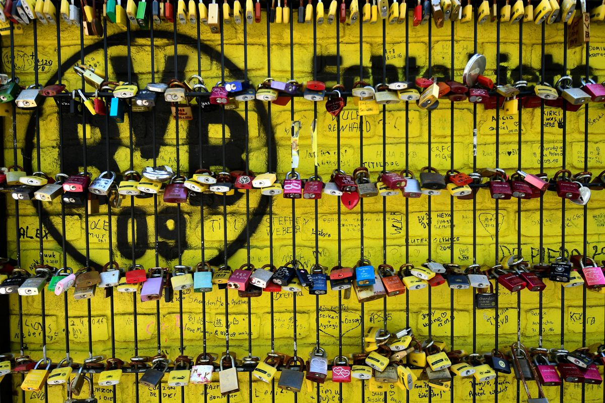 A picture taken on May 14, 2020 shows love locks on a fence in front of the Signal Iduna Park stadium of Bundesliga football club Borussia Dortmund in Dortmund, western Germany.