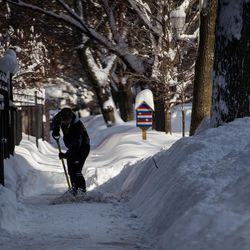 A person shovels snow on the sidewalk in the Edgewater neighborhood, Tuesday morning, Feb. 16, 2021, after a snowstorm dumped over a foot of snow in Chicago starting Sunday night. Snow is expected to continue to fall until Tuesday night.