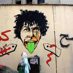 """A veiled Egyptian woman walks past newly painted graffiti that reads in Arabic """"erase more,"""" on a wall that was whitewashed during a cleanup campaign to erase old murals, in Tahrir Square, Cairo, Egypt, Wednesday, Sept. 19, 2012. Graffiti artists are repainting the walls in Mohammed Mahmoud Street, off Tahrir square, soon after municipal workers have whitewashed over a mural depicting the faces of victims of police brutality and violence over the past two years."""