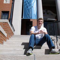 """This photo taken Sept. 20, 2012 shows Abraham Mulberry, an 18-year-old freshman, sitting on a campus hall step at Elmhurst College in Elmhurst, Ill. What a difference four years can make. In 2008, college campuses were filled with campaign posters and political rallies _ and frenzy. Remember """"Obamamania?"""" This year, it's difficult to find a college student who's truly excited about the presidential race."""