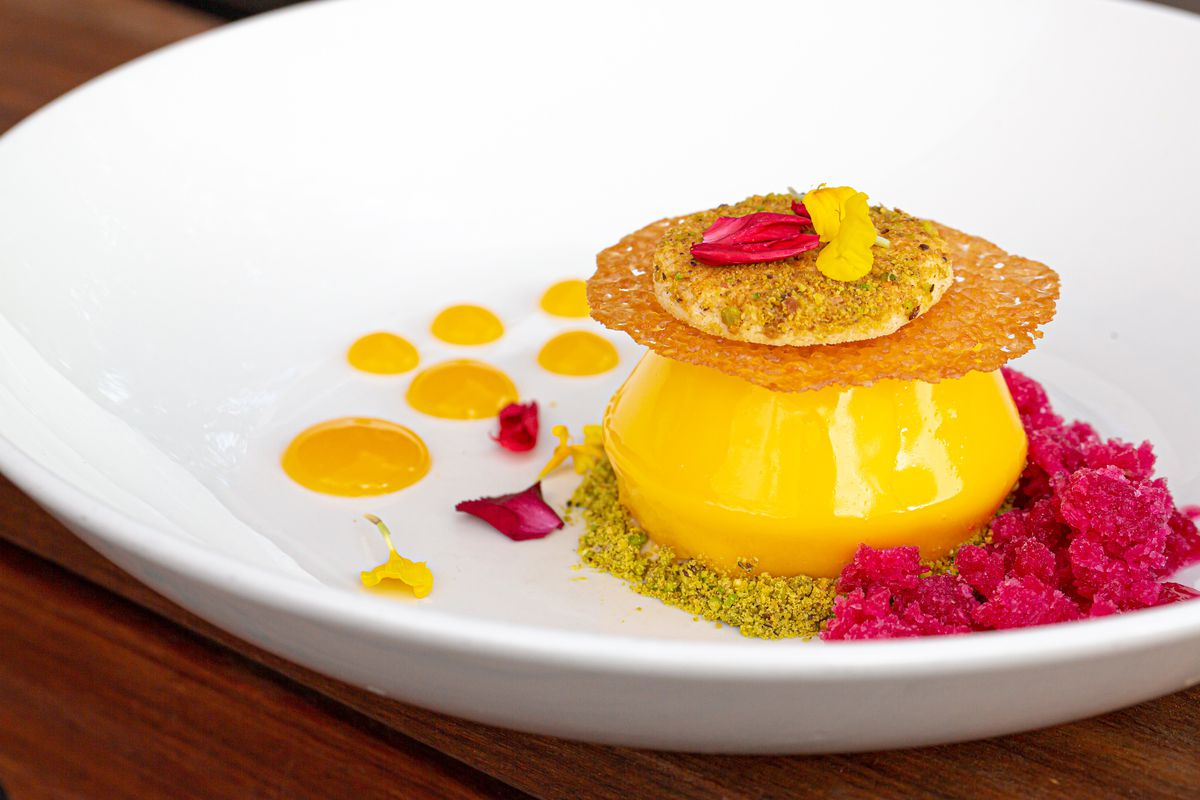 White plate containing dulce chocolate cream, passionfruit, pistachio, and prickly pear granita by Claudia Martinez