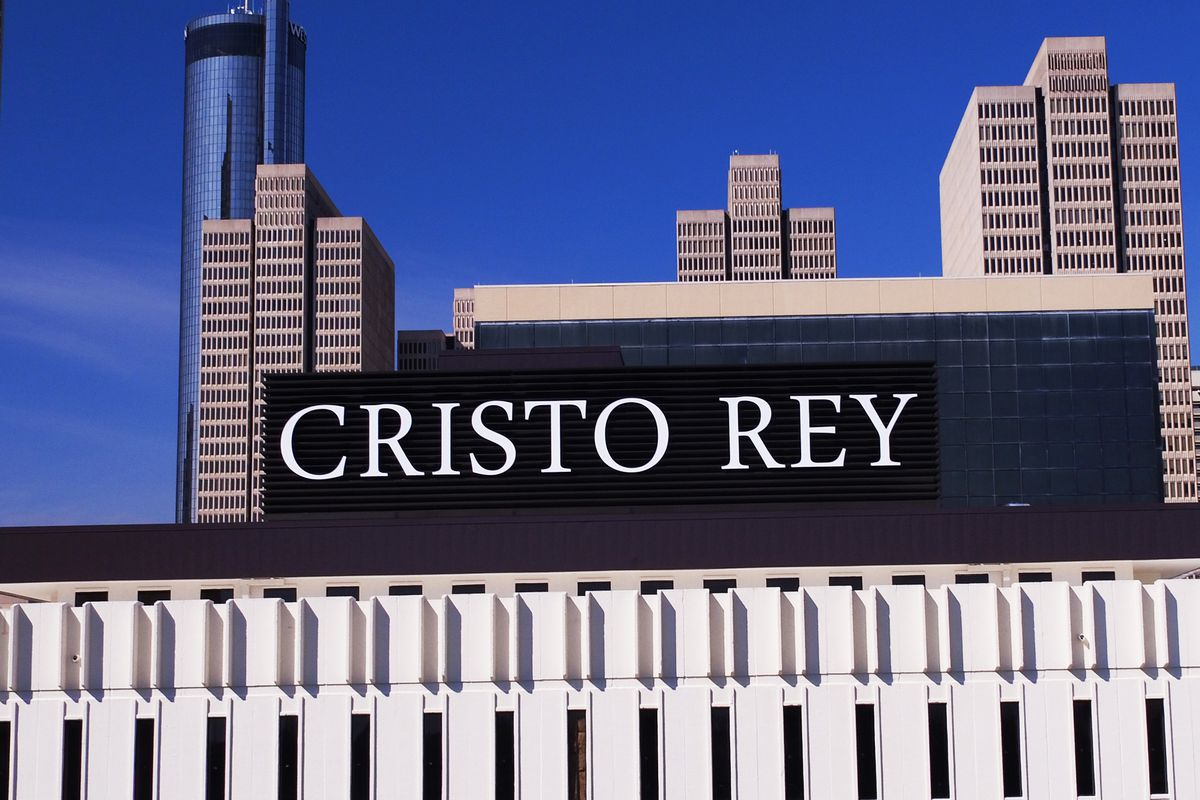 The Cristo Rey sign atop the building, with downtown skyscrapers beyond