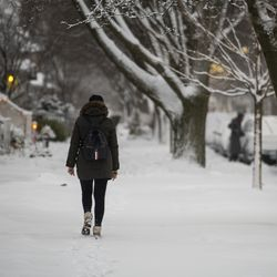 A woman walk along the sidewalk on West Glenlake Avenue in Edgewater as a winter snow storm batters Chicago, Tuesday morning, Jan. 26, 2021.