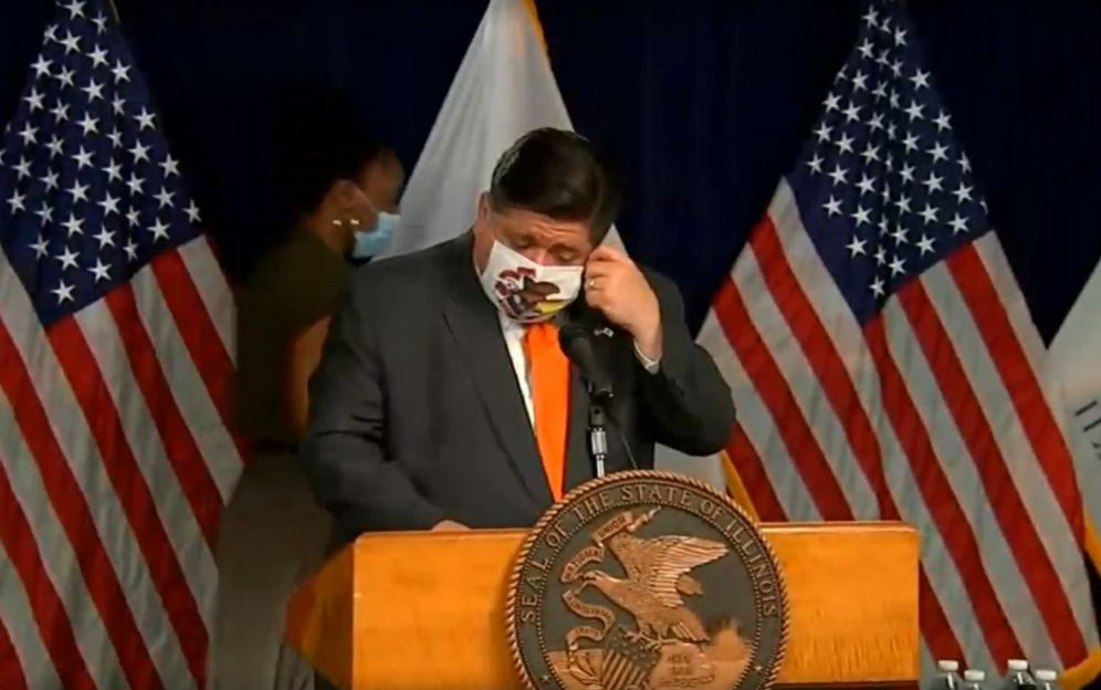 Gov. J.B. Pritzker removes his face mask before his  COVID-19 briefing at the Thompson Center on Wednesday.