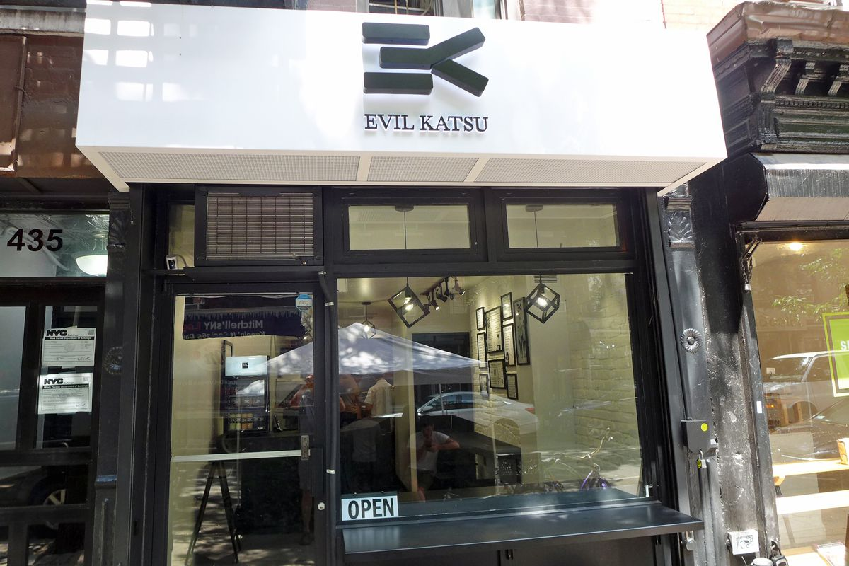 A white facade with the name of the restaurant in black at the top.