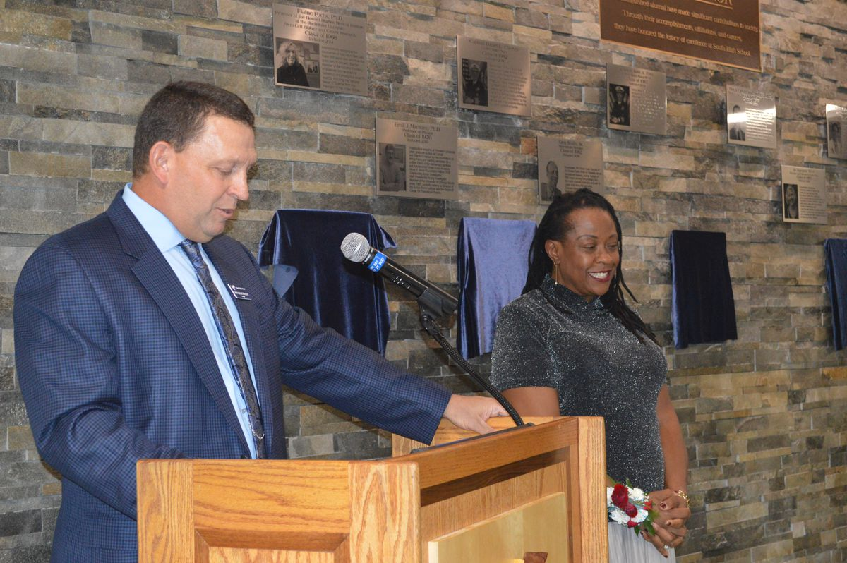 Principal Ed Schwartz inducts Sun-Times reporter Maudlyne Ihejirika into the Distinguished Alumni Wall of Fame. Ihejirika attended Downers Grove South in the late 1970s, a time when more minorities were moving into the suburbs seeking better housing and s