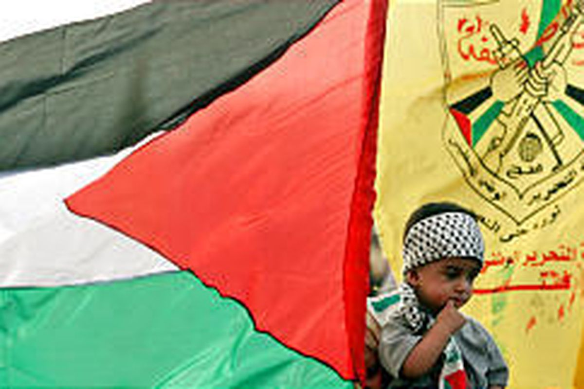 A Palestinian boy is carried by his mother past Palestinian and Fatah flags during a rally in southern Gaza Sunday celebrating Israel's pullout.