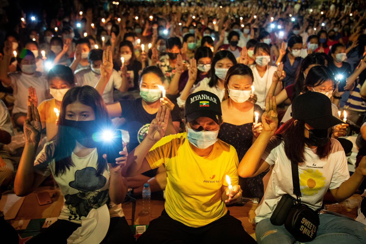 A mass of masked people sit in a nighttime street, illuminated by candles and cell phone lights. Many raise a three-fingered salute, which has come to signify the call for democracy in both Myanmar and Thailand.