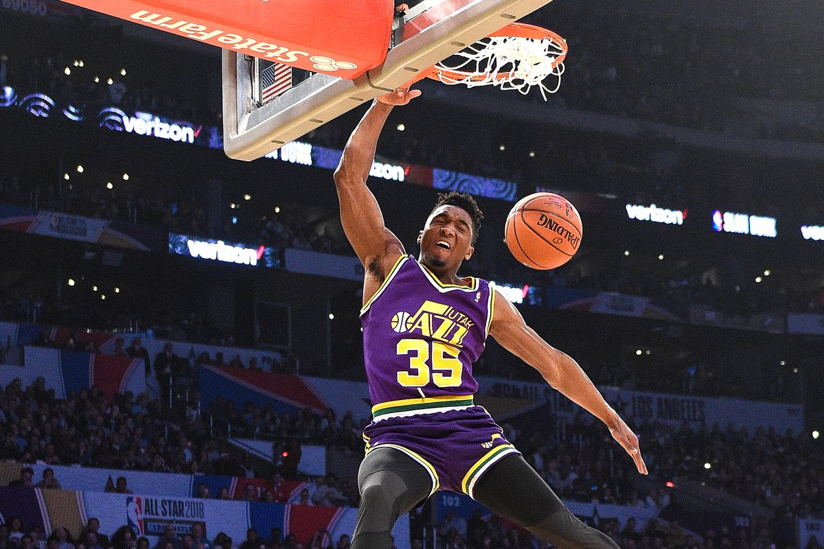 Donovan Mitchell dunks over Kevin Hart during the NBA's slam dunk contest