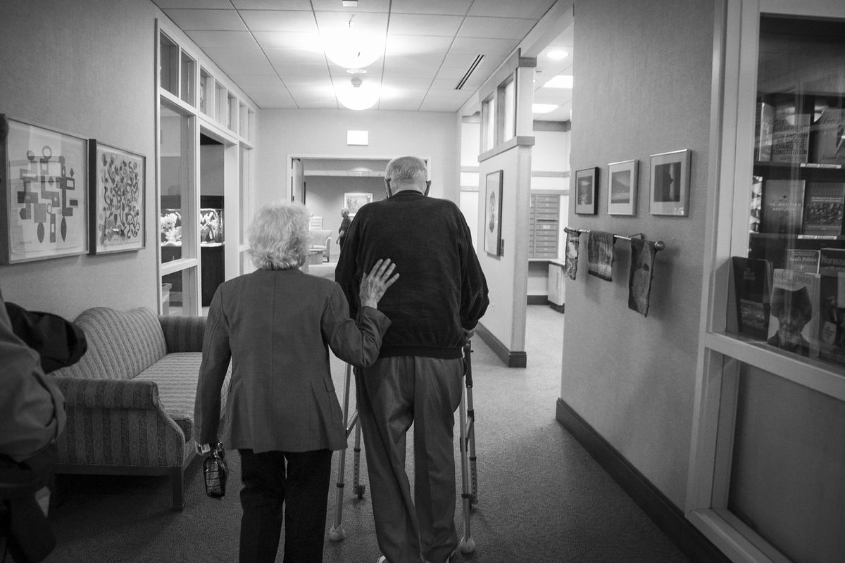 Evi Levin guides her husband Walter down a hallway at their home, Montgomery Place, in 2015. | Ashlee Rezin / Sun-Times