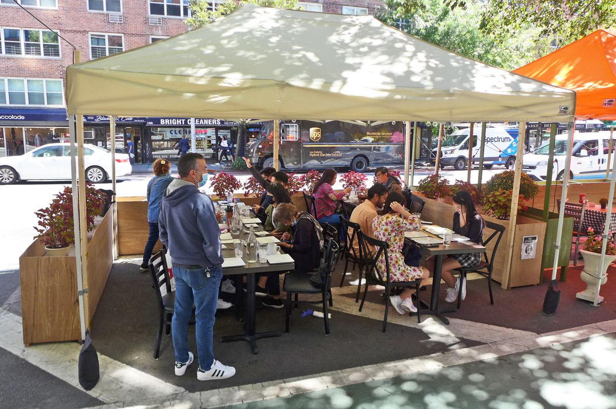 A pair of canvas tops in the street shelters a few tables where diner sit eating brunch.