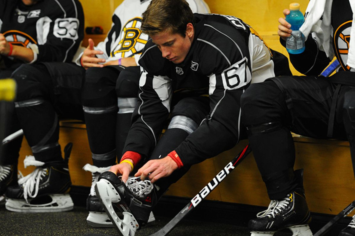 Peter Cehlarik laces his skates in the Bruins dressing room