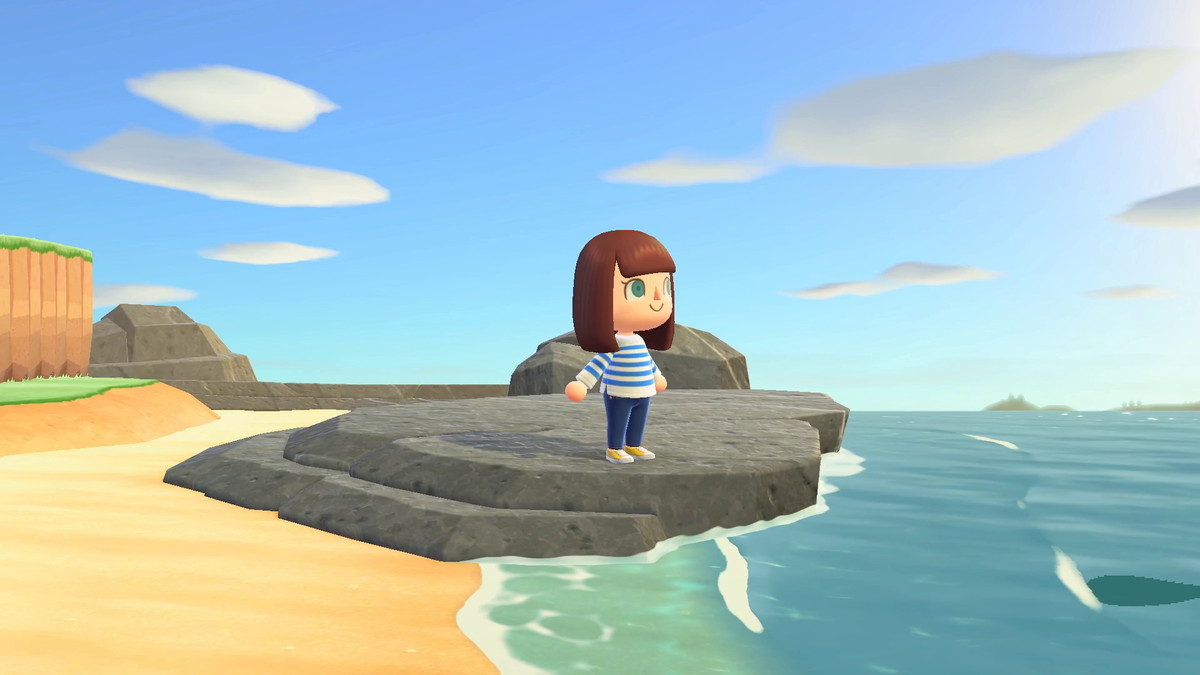 a brown-haired woman in a blue-and-white striped shirt and blue jeans stands on a stone platform on a beach in Animal Crossing: New Horizons