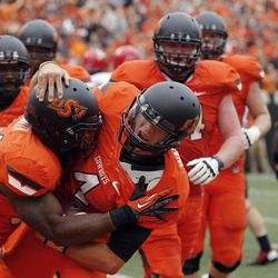 Oklahoma State quarterback J.W. Walsh (4) celebrates with running back Jeremy Smith, left, following a touchdown against Louisiana-Lafayette during the third quarter of an NCAA college football game in Stillwater, Okla., Saturday, Sept. 15, 2012. Oklahoma State won 65-24.