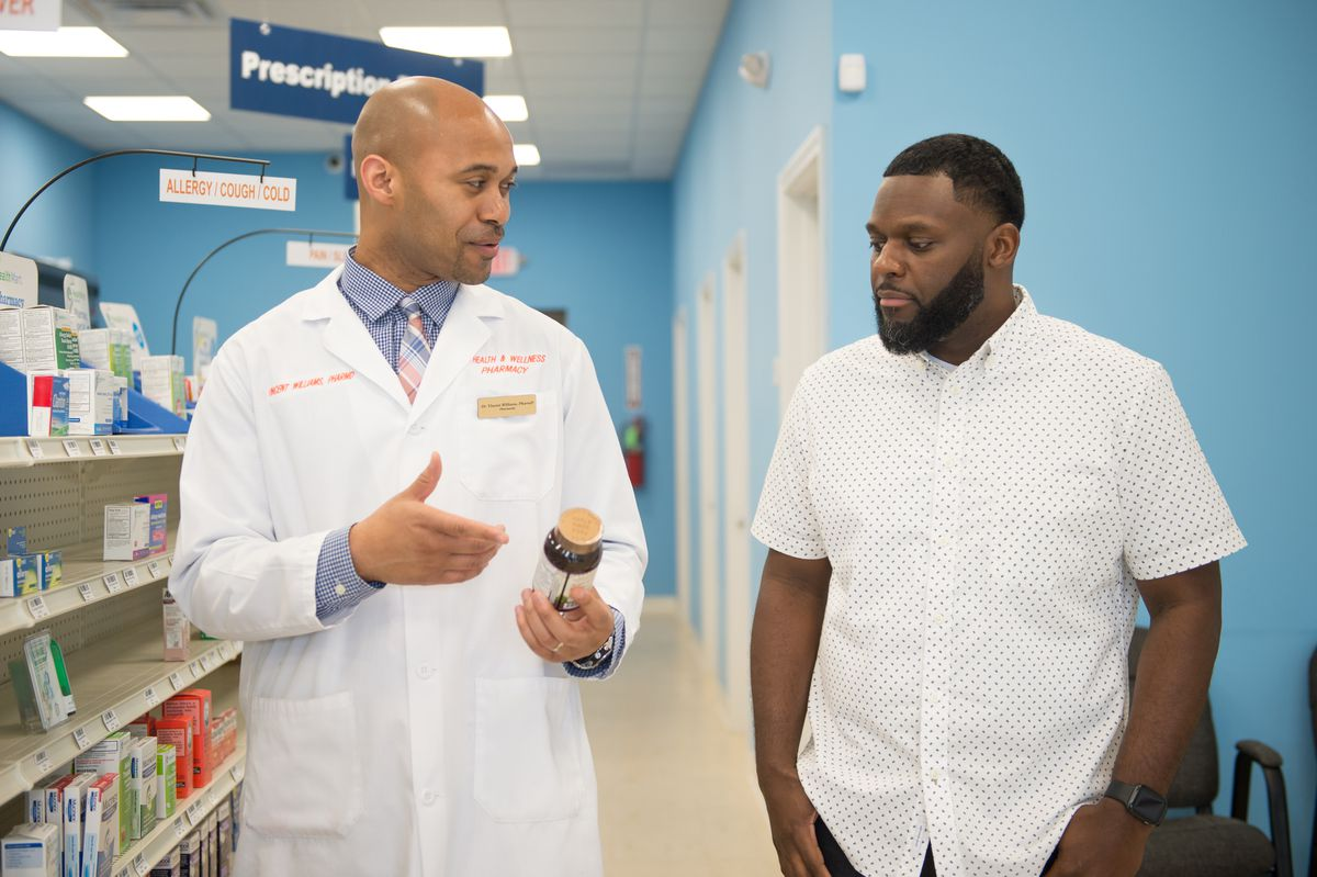Vincent Williams and Bernard Macon discuss medication at LV Health and Wellness Pharmacy in Shiloh, Ill., on June 6, 2019. (Michael B. Thomas for Kaiser Health News)