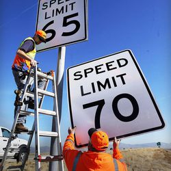Stephan Foster, top, and Jayson Kesler of UDOT change a 65 mph sign to 70 mph on I-80 west of Salt Lake City, Monday, Dec. 8, 2014.