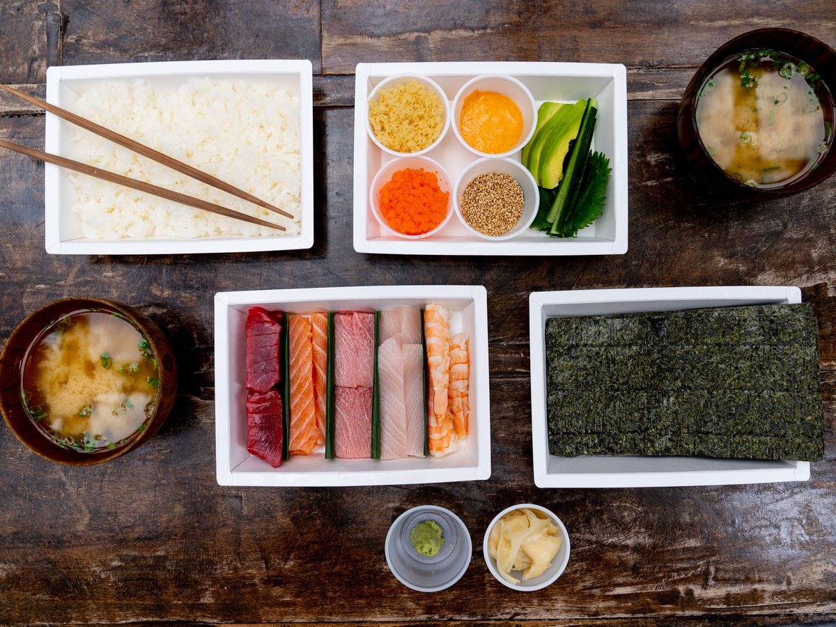 An overhead shot of a sushi handroll kit, including a plate of rice, sheets of seaweed, slices of protein like tuna and shrimp, seasonings and two bowls of soup. The food is laid out on a wooden table.